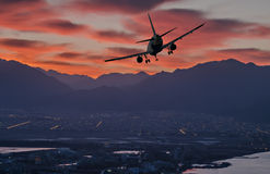 Silhouette of landing airplane at dawn Royalty Free Stock Photo