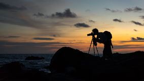 Silhouette of landscape photographer. Stock Images