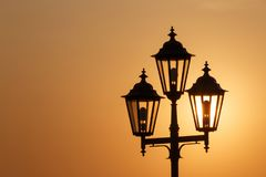 Silhouette of lantern against rising sun Stock Photos
