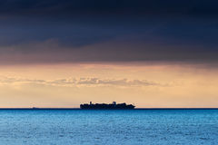 Silhouette of large container ship crossing Baltic sea under dramatic dark nimbostratus cloud formation. Silhouette of large container ship on the horizon Royalty Free Stock Images