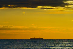 Silhouette of large container ship on the horizon. Royalty Free Stock Photo