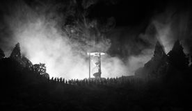 Silhouette of a large crowd of people in forest at night standing against a big hourglass with toned light beams on foggy backgrou Royalty Free Stock Photos
