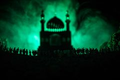 Silhouette of a large crowd of people in forest at night standing against a blurred mosque building with toned light beams on fogg Stock Images