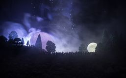 Silhouette of a large crowd of people in forest at night watching at rising big full Moon. Decorated background with night sky wit. H stars, moon and space stock photo