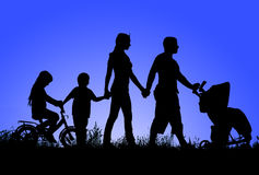 Silhouette of a large family that walks at sunset Stock Image