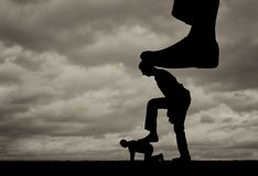 Silhouette of a large leg presses on a man who also presses his foot on another man lying on the ground stock photos