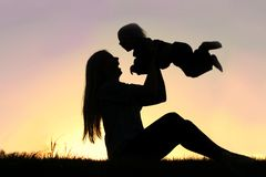 Silhouette of Laughing Mother and Baby Playing Out Stock Photos