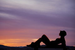 Silhouette lay back cowgril outdoors Royalty Free Stock Images