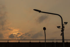 Silhouette LED Light poles and cctv on an Expressway with orange Stock Photo