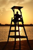 Silhouette of a lifeguard at sunset. The silhouette of a Baywatch gone up in his chair with the sunset in the background Stock Photos