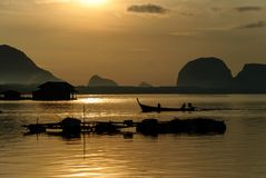 Silhouette Lifestyle Fisherman On Boat Fishing in Morning Golden Stock Images