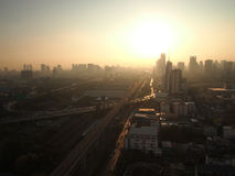 The silhouette light behind Bangkok city. The sun is rising in the end of the railway in the middle of Bangkok City, Thailand Royalty Free Stock Photography