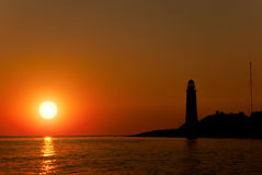Silhouette of a lighthouse on the background of the setting sun Royalty Free Stock Image