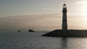 Silhouette of lighthouse with fishing boat stock video footage