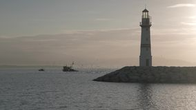 Silhouette of lighthouse with fishing boat stock footage