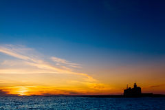 Silhouette of a lighthouse at sunset. Silhouette of a lighthouse at golden sunset stock photography