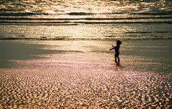 Silhouette of a little baby girl in front of the sea Royalty Free Stock Photos