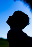 Silhouette of little boy against blue sky. Profile silhouette of a young boy of age eight who is looking upward.  His hair has cute cowlicks.  He could be Stock Image