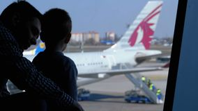 Silhouette of a little boy and father in front of the terminal window looking at the planes. Boryspil, Ukraine, April 3, 2019: silhouette of a little boy and stock footage