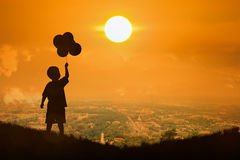 Silhouette of little boy  hold bubble look at  the sun Royalty Free Stock Photos