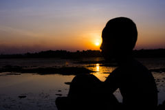 Silhouette of a little boy hugged her knees on evening sunlight at the edge of the swamp. Stock Photography