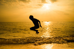 Silhouette of little boy jumping over Stock Photography