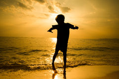 Silhouette of little boy jumping over the beach wave sunshine Royalty Free Stock Photos