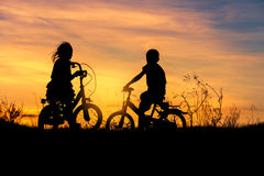 Silhouette little boy and little girl riding bike on sunset Royalty Free Stock Photos