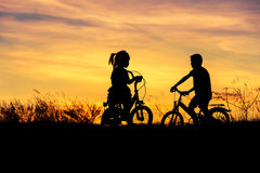 silhouette little boy and little girl riding bike on sunset Stock Photos