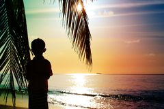 Silhouette of little boy looking at sunset on beach. Silhouette of little boy looking at sunset on tropical beach Stock Photo