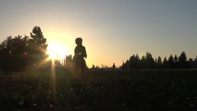 Silhouette of little boy running at sunset stock footage