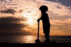 Silhouette of little boy on scooter against background of sea sunset Royalty Free Stock Image