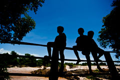 Silhouette Little boy sitting on a fence at Khone Phapheng water Royalty Free Stock Photos