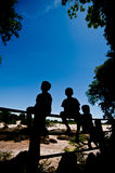Silhouette Little boy sitting on a fence at Khone Phapheng water. Fall or mekong river in champasak southern of laos one of the biggest and beautiful waterfall stock images