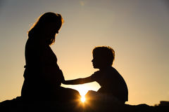 Silhouette of little boy touching pregnant mother tummy royalty free stock photos