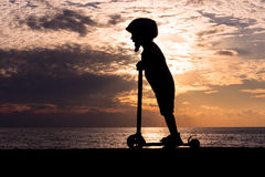 Silhouette of little boy wearing helmet on scooter on background of sea sunset Royalty Free Stock Photography