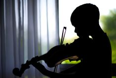 Silhouette Little boys play and practice violin in music class room. Silhouette Little boys play and practice violin in the music class room Royalty Free Stock Images