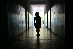 Silhouette of the little girl. In a long corridor Stock Photo
