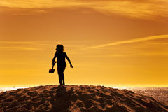 Silhouette of little girl on beach in sunset Royalty Free Stock Photo