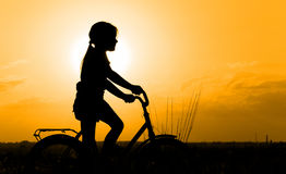 Silhouette of little girl on a bicycle. Backlit by sunset Royalty Free Stock Photos