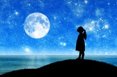 Silhouette, little girl child standing on a hill by the sea looking at the starry sky. stock photo