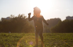 Silhouette of little girl dancing at sunset Stock Photography