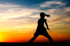 Silhouette of little girl dancing on sunset sky background Stock Photography