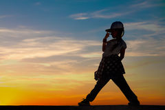 Silhouette of little girl dancing on sunset sky background Royalty Free Stock Images