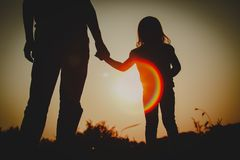 Silhouette of little girl holding parent hand at sunset royalty free stock photo