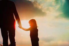 Silhouette of little girl holding parent hand at sunset. Sky stock images