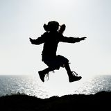 Silhouette of a little girl jumping Stock Photography