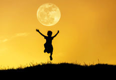 Silhouette little girl jumping to sky on sunset with full moon. Royalty Free Stock Images