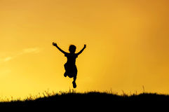 Silhouette little girl jumping to sky on sunset Stock Photo