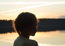 Silhouette of little girl on the lake at sunset. Royalty Free Stock Photos